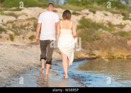 Glückliche romantische mittleren gealterten paar schönen Sonnenuntergang genießen Fuß am Strand. Reisen-Urlaub-Ruhestand-Lifestyle-Konzept - Stockfoto