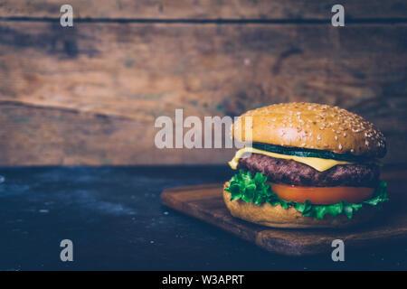 Hausgemachte Burger (Cheeseburger) mit Rindfleisch und Gemüse auf einem Holz- Hintergrund. Klassische hausgemachte Burger. Close Up, kopieren. - Stockfoto