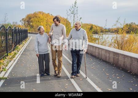 Ein älteres Paar Spaziergänge im Park mit einem männlichen Assistenten oder erwachsenen Enkel. Pflege für ältere Menschen, Freiwilligenarbeit - Stockfoto