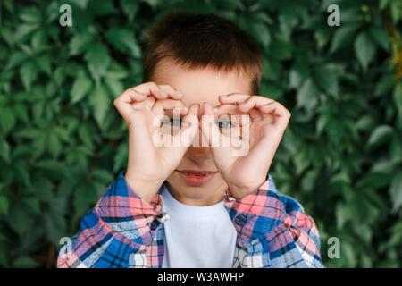 Kleiner Junge macht OK Geste und schaut durch die Hand an Kamera im Freien