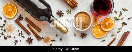 Winter Gewürze für Glühwein auf weißem Hintergrund, Ansicht von oben, Banner. Saisonale Glühwein Zutaten-Aroma, Gewürze und eine Flasche Rotwein. - Stockfoto