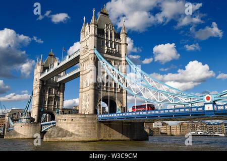 Twin stone Towers der Tower Bridge über die Themse in London mit roten Bus und blaue und weiße Suspension Bridge und erhöhten Fußgängerweg - Stockfoto
