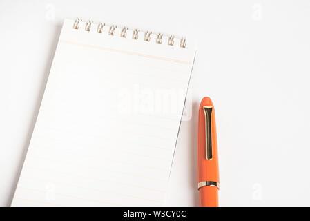 Ein glänzendes orange Füllhalter zusammen mit einer Spirale regiert - Notebook gebunden. - Stockfoto
