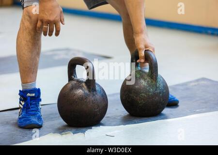 Athlet im Gewichtheben. Zwei Gewichte von 24 kg. - Stockfoto