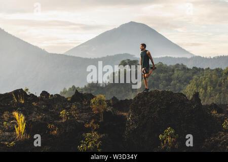Mann tun, Stretching und Vorbereitung für Workout und Laufen im Freien. Super Blick auf die Berge im Hintergrund. Abenteuer Sport Konzept.