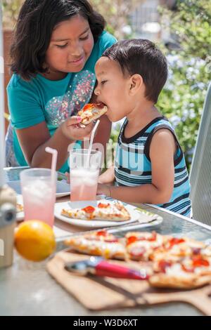 Geschwister genießen Sie zum Mittagessen im Freien, während die große Schwester füttert ihr kleiner Bruder ein Stück Pizza. - Stockfoto