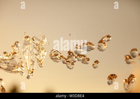 Wassertröpfchen in der Luft mit Spritzern und Kette Blasen auf eine goldene und bronzene isoliert Hintergrund in der Natur eingefroren. Klare und transparente Flüssigkeit sy - Stockfoto