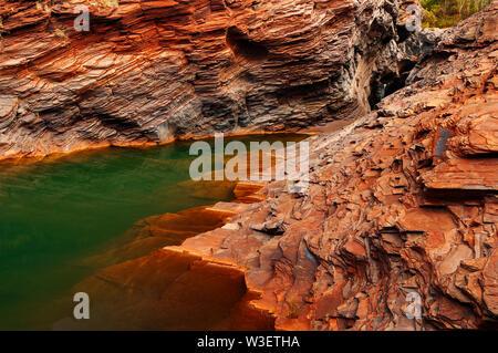 Karijini National Park ist, wo das grüne Wasser erfüllt die roten Felsen.