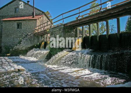 Dam an der alten Wassermühle aus Steinen. Schöne Ströme von Wasser, einen kleinen Wasserfall. Über die Staumauer ist eine alte Holzbrücke. Blue Clear Sky. - Stockfoto
