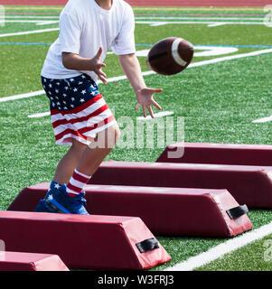 Ein Junge ist im Sommer Fußball-Camp fängt einen Fußball, während seitlich laufen über den roten Barrieren und das Tragen der roten, weißen und blauen Flagge Shorts und so - Stockfoto