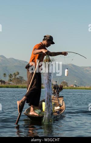 INLE SEE, MYANMAR - 28. NOVEMBER 2018: Vertikale Bild der lokalen Fischer Holding die Paddel mit Bein Fisch mit traditionellen Technik in Inle la - Stockfoto