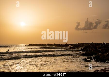 Wellen schlagen die Felsen wie die Sonne nähert sich der Einstellung - Stockfoto