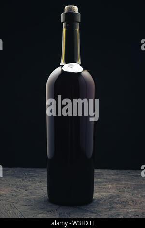 Flasche Rotwein auf einem dunklen Holztisch schwarzen Hintergrund behaid. - Stockfoto