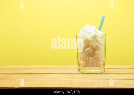 Glas voller Würfel Zucker mit Stroh auf einen hölzernen Tisch schön gelb hinterlegt - ungesunde Ernährung Konzept. - Stockfoto