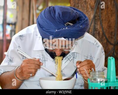 Im mittleren Alter Thai Sikh Mann mit blauen Turban der Sikhs (Dastar) isst gelben Nudeln mit Kunststoff Sticks und einem chinesischen Edelstahl Kelle hacken. - Stockfoto