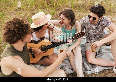 Gruppe von Fröhlichen Freunden Ausgabe Zeit zusammen im Freien, trinken Bier, Gitarre spielen - Stockfoto
