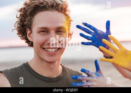 Fröhlicher junger Mann am Strand, Feiern mit bunten Holi Farbe - Stockfoto