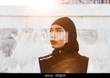 Bild einer jungen konzentrierten muslimischen Sport Fitness Frau in Hijab und dunkle Kleidung posiert im Freien gekleidet. - Stockfoto