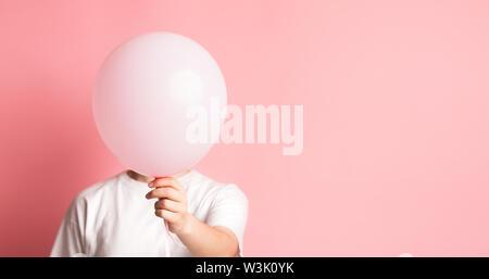 Frau verbergen ihr Gesicht neben Rosa Ballon mit Leerzeichen - Stockfoto
