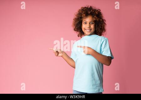 Lustige jugendliche Mädchen Pointing Finger weg auf freien Speicherplatz - Stockfoto