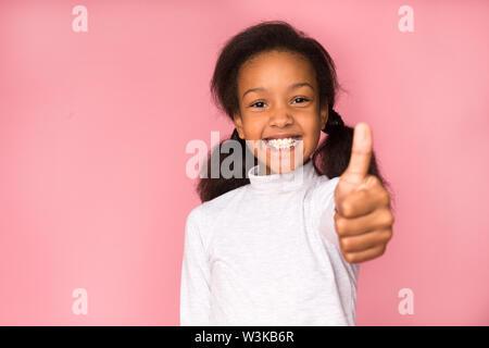 Happy girl, Daumen hoch, auf rosa Hintergrund - Stockfoto