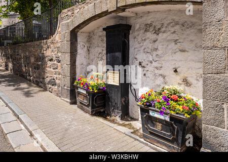 Blumenschmuck neben einem alten öffentlichen Wasserpumpe vom 1918 in der pollett unter La Plaiderie, St Peter Port, Guernsey, Kanalinseln, Großbritannien