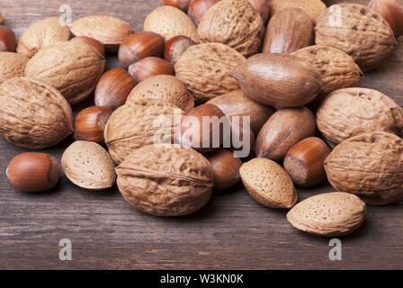 Nahaufnahme der verschiedenen Arten von getrockneten Früchten einschließlich pekannüsse, Mandeln und Haselnüsse in der Schale auf rustikalen Holztisch - Stockfoto