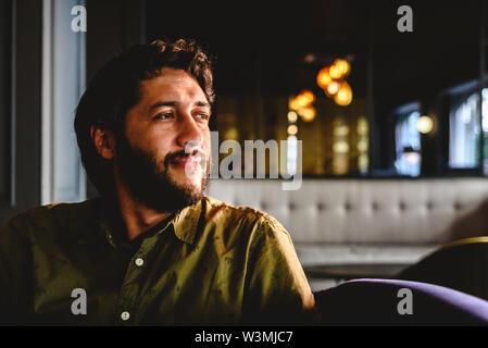 Junger Mann mit lateinischen Bart bis unendlich über das künftige Geschäft denken. - Stockfoto