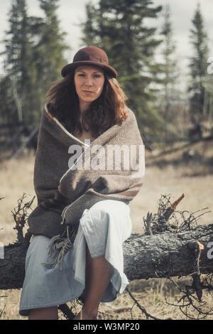 Eine attraktive junge Frau sitzt auf einem Baumstamm in eine Wolldecke eingewickelt. Yukon Territory, Kanada - Stockfoto