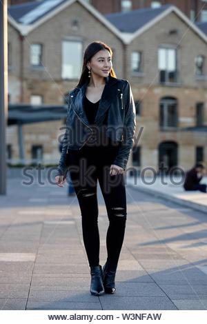 Junge Frau mit schwarzen stehend an Kamera schaut auf Sonnenuntergang am Circular Quay, Sydney. - Stockfoto