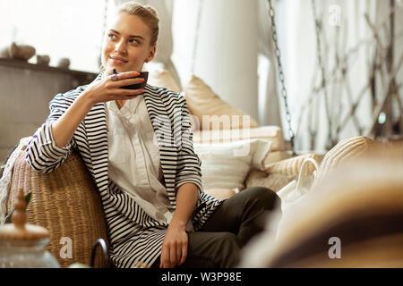 Die Teekanne. Strahlende blonde Frau in schwarzen Hosen ruht auf einem Sofa und immer frischen Kaffee aus einer Teekanne - Stockfoto