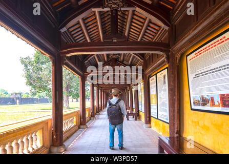 Touristen besuchen Spaziergang entlang der Holz- Flur Flure der Thai Hoa Palace in der Kaiserstadt in Hue, Vietnam.