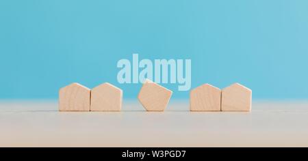 Immobilien- und Wohnungswirtschaft Immobilienmarkt Konzept mit Holzhaus Modell auf blauem Hintergrund Stockfoto
