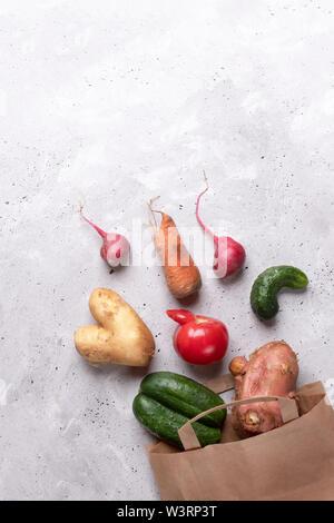Satz Reifen hässlich Gemüse in Diagonalen von papiertüte verstreut auf grauem Beton Hintergrund. - Stockfoto