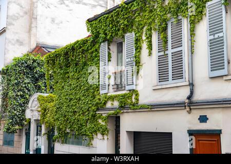 Haus mit grünen Reben an der Wand und Rollläden in Paris, Frankreich - Stockfoto