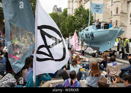 Aussterben Rebellion blau Boot Polly Higgins bei Störungen über 5 britische Städte fordert Regierung auf, jetzt zu handeln außerhalb der Royal Courts of Justice, nachdem es letzte Woche wurde bekannt, dass mehr als 1.000 Aktivisten, die in den vorhergehenden Demonstrationen teilgenommen Verfolgung konfrontiert waren, am 15. Juli 2019 in London, England, Vereinigtes Königreich. Aussterben Rebellion ist ein Klimawandel Gruppe begann im Jahr 2018 und hat eine riesige Fangemeinde von Leuten zu friedlichen Protesten begangen. Diese Proteste sind die Hervorhebung, dass die Regierung nicht genug um die katastrophalen Klimawandel zu vermeiden und zu verlangen. - Stockfoto