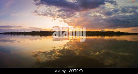 Wunderschöner Sonnenuntergang Panorama über die Stadt Horizont mit Reflexion über die ruhige See Wasser in einem stillen Sommerabend. - Stockfoto