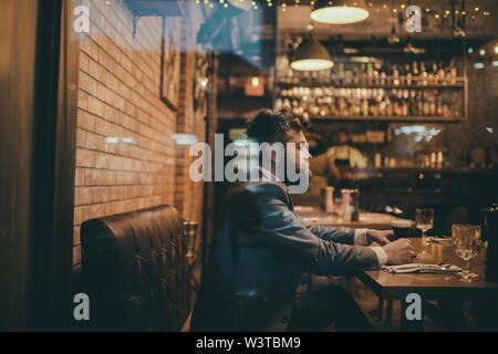 Bärtiger Mann im Restaurant mit Bier Glas. Schwere bar Kunden sitzen im Cafe trinken Bier. Datum treffen der Hipster in Pub erwartet. Bier Zeit - Stockfoto