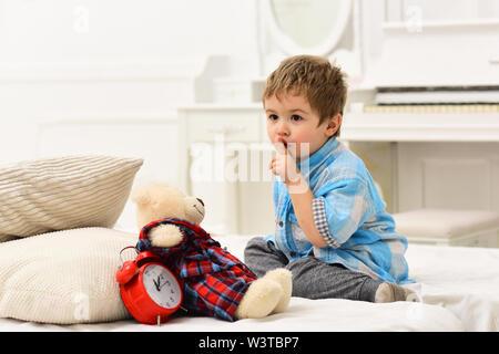 Kind im Schlafzimmer mit Stille Geste. Junge mit ruhigen Gesicht setzt Lieblingsspielzeug auf dem Bett, Zeit zum Schlafen. Kid, Plüschbär in der Nähe von Kissen und Wecker - Stockfoto