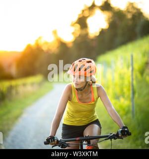 Hübsche, junge Frau Radtouren mit dem Mountainbike genießen, gesunden, aktiven Lebensstil im Freien im Sommer (flacher DOF)