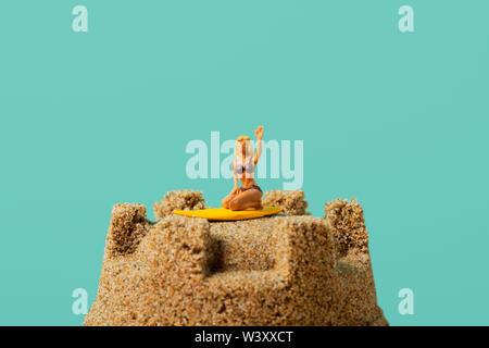 Nahaufnahme von einer Miniatur Frau im Badeanzug, kniet auf einem Surfbrett, auf dem Gipfel eines Sandcastle, vor einem blauen Hintergrund mit einem großen leeren Raum auf t - Stockfoto