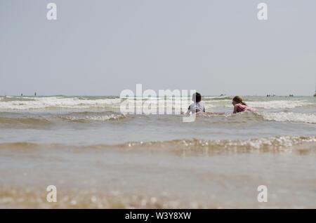 Zwei Kinder von Hinter dem Spielen im flachen Wellen Stockfoto