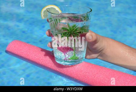 Junge Frau mit einem kühlen Getränk schwimmt auf einem Pool Nudel in einem Schwimmbad. Sommer vibes, cool Bleiben, Spaß haben. - Stockfoto