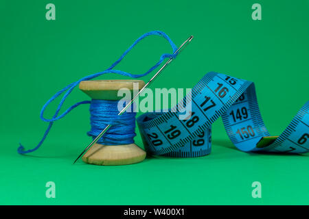 Eine Nahaufnahme Bild von einem Maßband, Spule mit blauem Faden und Nähnadel auf grünem Hintergrund, Handarbeit Nähen, Handarbeiten und Schneiderei Konzept - Stockfoto