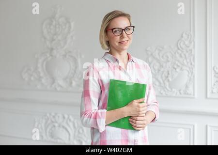 Beatifull girl Plaid Shirt hält Buch in die Hände und lächelte. - Stockfoto