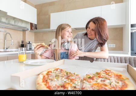 Mutter und Tochter in der Küche sitzen, essen Pizza und Spaß haben. Fokus auf Tochter