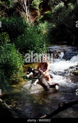 Blonde Frau, Baden im Fluss mit sibirischen Husky Hund. - Stockfoto