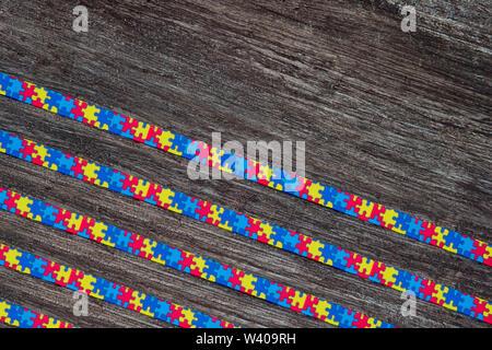Welt Autismus Bewußtsein Tag mit Puzzle Band auf Holz- Hintergrund - Stockfoto