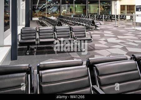 Leere schwarze Sitze am Flughafen Gate Terminal - Stockfoto