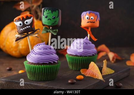 Festliche Halloween cupcakes dekoriert mit Marshmallow in Schokolade oder Kuchen und Süßigkeiten. Lustige monster Gesicht behandelt. - Stockfoto
